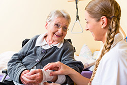 Nurse taking care of senior woman in retirement home bandaging a